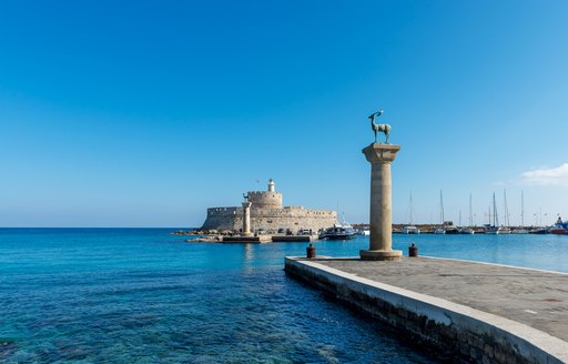 statues at entrance to port in greece
