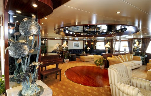 Superyacht Lauren L main salon, with grand piano and lounging areas