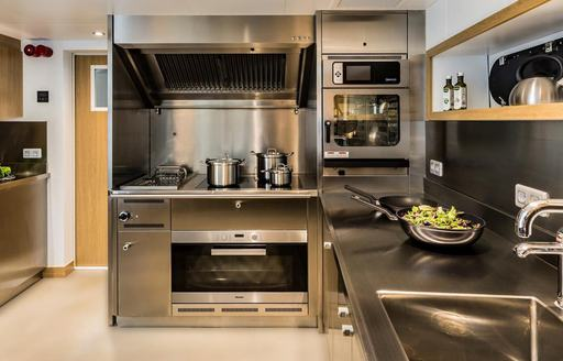 Stainless steel galley of Game Changer yacht with oven and pots on hob visible