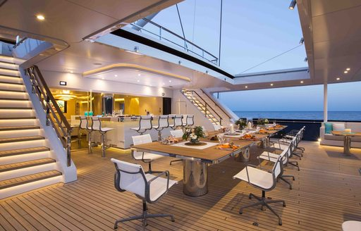 social area on aft deck of luxury charter yacht aquijo,with large dining table and alfresco bar