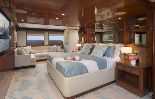 rich wooden wall panels and large bed facing a TV in the master suite aboard luxury yacht Time For Us