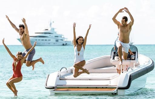 a family on their superyachts tender jumping into the Mediterranean sea