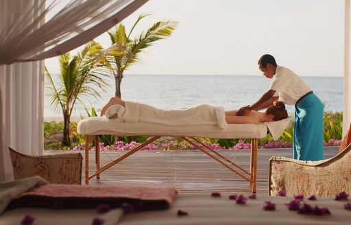 woman lays on table and receives a massage from staff on thanda island