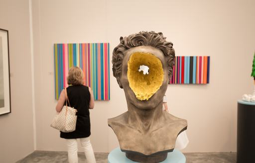 A sculpture on display at Art Basel Miami gallery, paintings in background with female charter guest viewing.