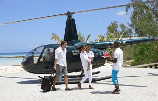family get out of helicopter on thanda island