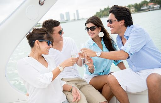 four friends enjoy champagne while on a superyacht cruising in Miami