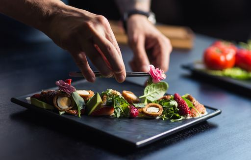 Chef garnishes plate of food with flower