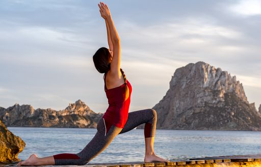 Woman enjoys yoga session with Es Vedra in distance