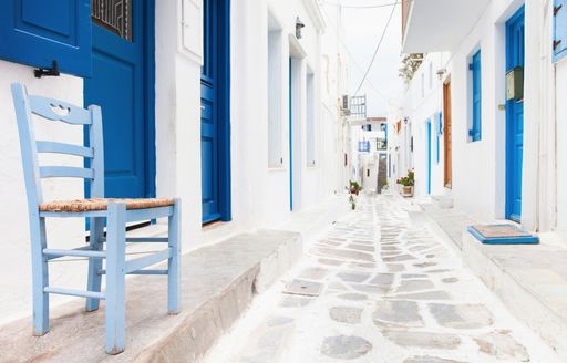 White houses and blue doors in a cobbled alleyway in Greece