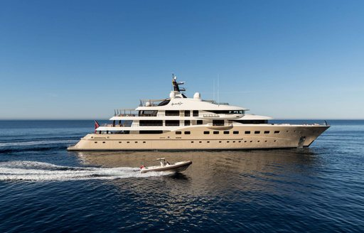 Motor yacht Here Comes the Sun underway, with tender alongside