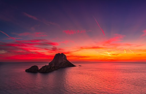 View from Ibiza at sunset to rocky outcrop and calm sea