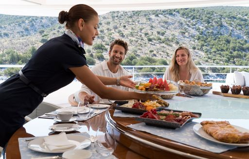 Couple being served food on superyacht O'PARI