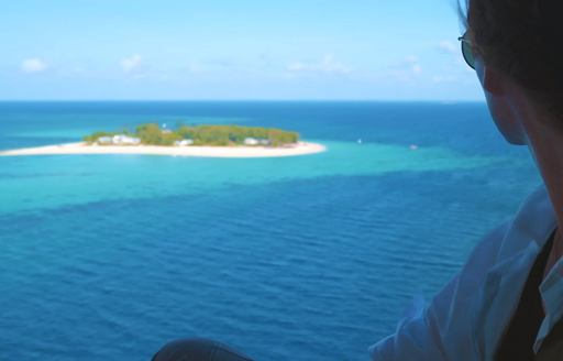 woman looks out at thanda island from helicopter window