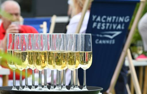 tray of champagne in foreground with deck chair decorated in Cannes Yachting Festival logo