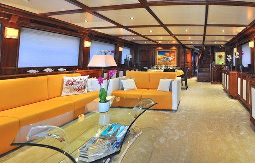 Yellow sofas and cream carpet in main salon of yacht CONQUISTADOR