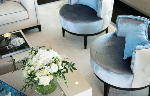 seating on superyacht spirit, with flowers and blue velvet chairs