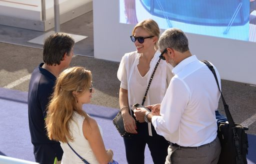 Group of show-goers stand with yacht broker at Cannes Yachting Festival