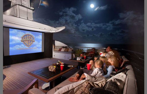 Sundeck cinema onboard Superyacht LIND, widescreen facing sofa seating at night, surrounded by sea