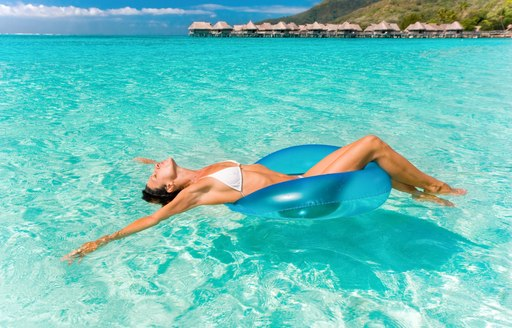 luxury charter guest swims in the waters of Tahiti