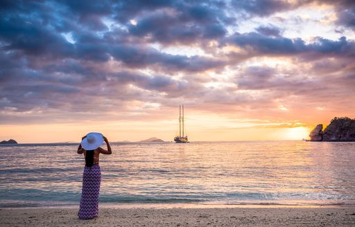 Charter guest stands on beach looking at LAMIMA yacht