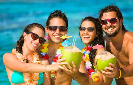 Four young people drink cocktails on a tropical beach