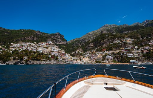 yacht in front of town of positano on the amalfi coast
