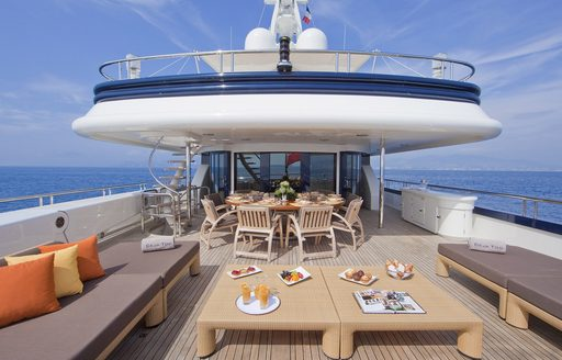 alfresco dining area and seating on the upper deck aft of luxury yacht Deja Too