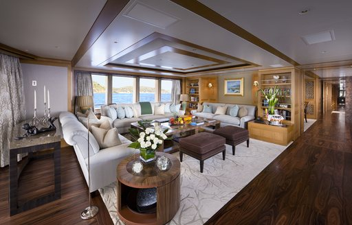 Main salon onboard Charter Yacht 'Lady Britt', U shaped seating around coffee table, with bookshelves and far reaching corridor