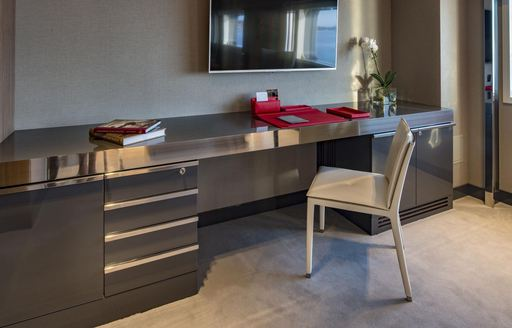 Office facilities within guest cabin onboard M/Y SERENITY, desk and stationary with white upholstered chair