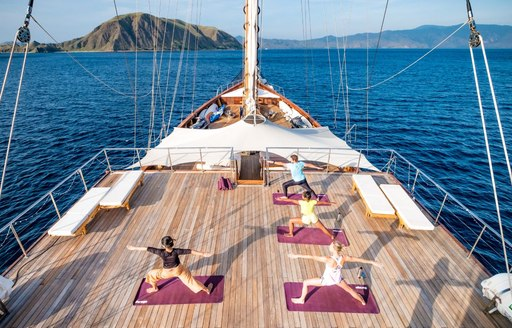 Guests of LAMIMA yacht doing yoga session on deck aerial shot