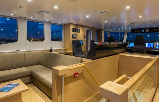 Wooden decked interior of Game Changer yacht and staircase and sofas