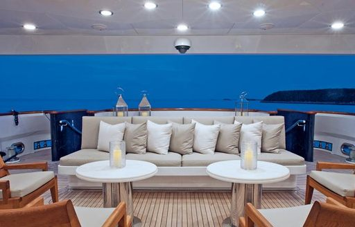 social seating on main deck aft of luxury motor yacht alessandra, with sofas in front of cocktail tables with candles in centre