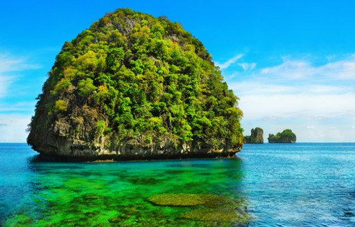 Conical green islet in shallow water of Loh Sama Bay, Ko Phi Phi, Thailand