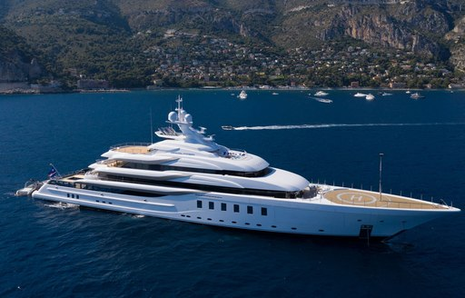 long shot of superyacht madsummer sailing by the coast of of tropical location
