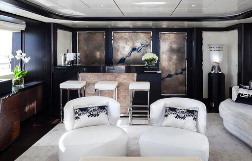 Elegant skylounge on superyacht Lady Li, with bar and textured artwork