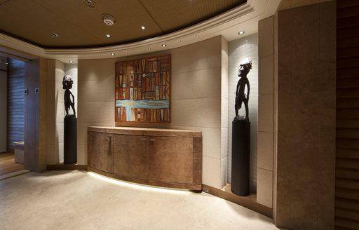 statues in corridor on naia superyacht