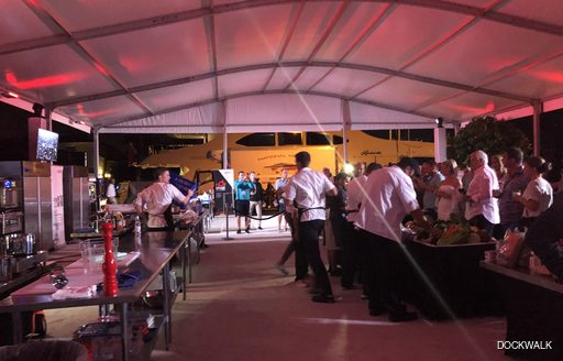 Yacht chefs cooks while show-attendees look on