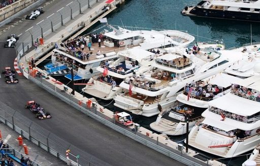 Yachts overlooking the race track at the Monaco Grand Prix as four cars race past