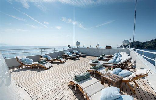 Sunloungers on large teak deck of superyacht Bleu De Nimes