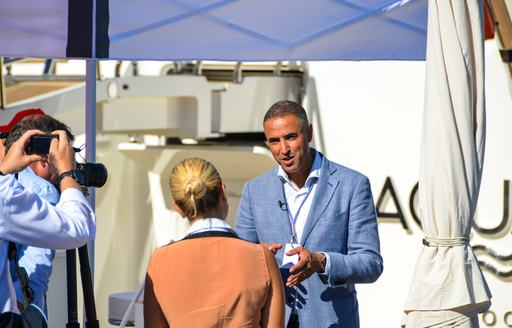 man discusses matters with woman during monaco yacht show