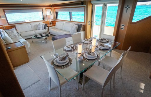 Interior of charter yacht NOMADA, with dining table and sofas visible