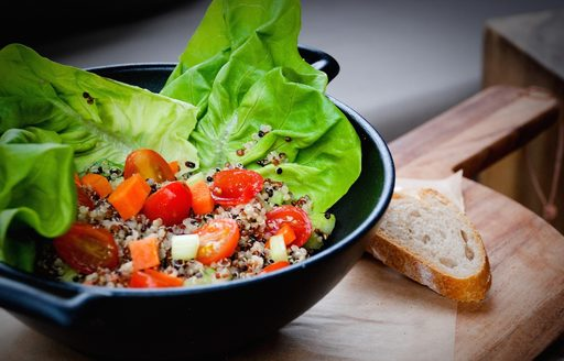 A tomato and lettuce salad on a wooden chopping board with a slice of bread