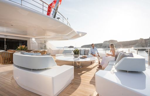 Couple sitting on aft deck of superyacht O'PARI on light colored furnishing in sun