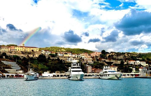 Yachts in Cala del Forte Marina, with a rainbow behind