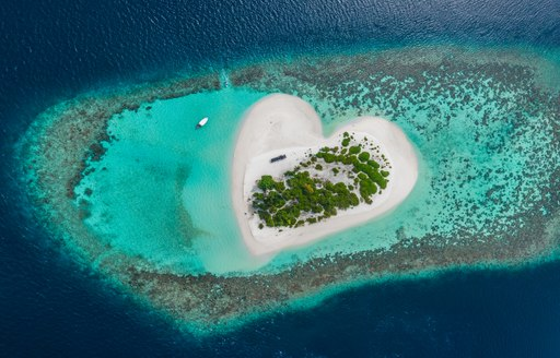Aerial view of heart shaped island in the Maldives, surrounded by a coral reef separating azure and sapphire waters.