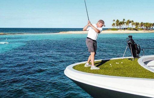Man plays golf on bow of luxury superyacht