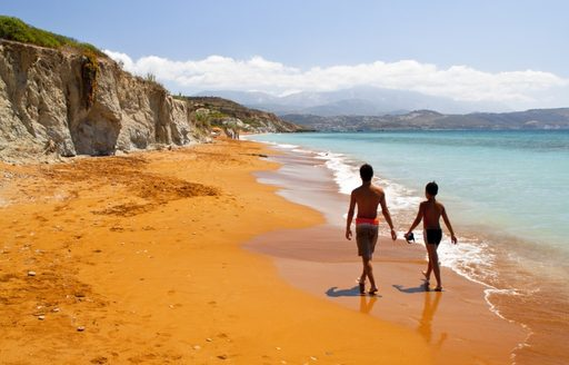 People walking along a secluded red sand beach in Greece
