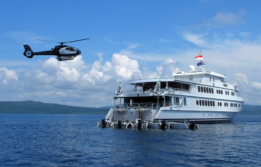 helicopter hovering above motor yacht True North when on a luxury yacht charter in the Whitsundays