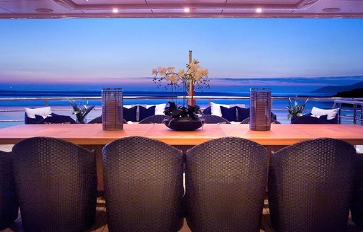 View across deck dining table to sea on superyacht Sea Rhapsody