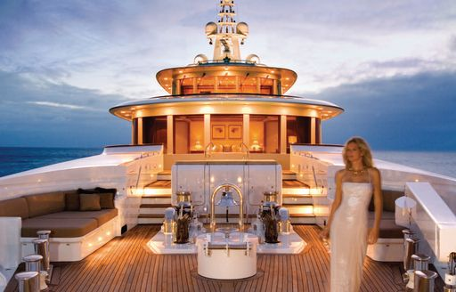 Charter guest on the sundeck of luxury yacht UTOPIA at night, illuminated by lighting panels